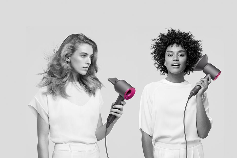 Two ladies drying their hair with the Dyson Supersonic. One has the diffuser attachment.