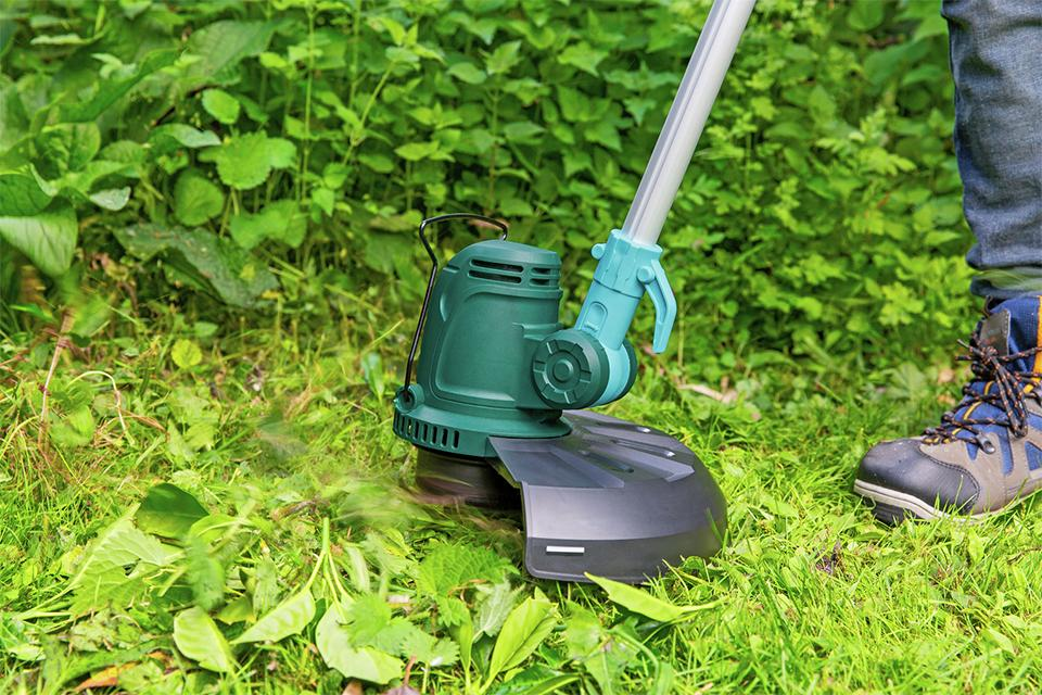 Gardener using a McGregor grass trimmer to strim grass and weeds.