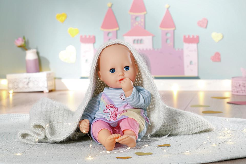 Baby Annabelle doll sat in fairytale castle themed room with blanket draped over them.