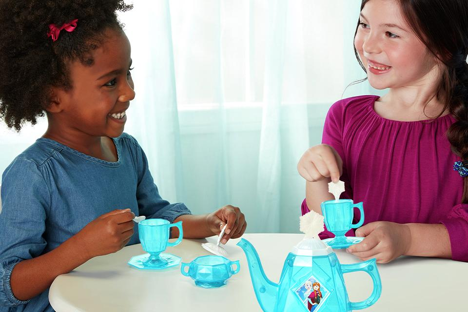 Two girls having a tea party with a frozen tea set.