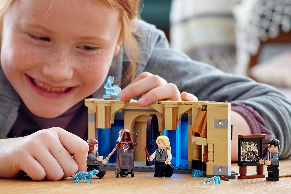 Close up of a smiling girl playing with a Harry Potter Lego set.