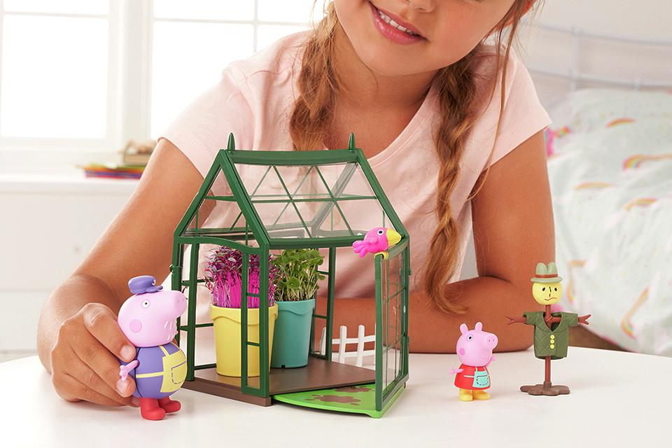 Little girl playing with Peppa Pig gardening playhouse.