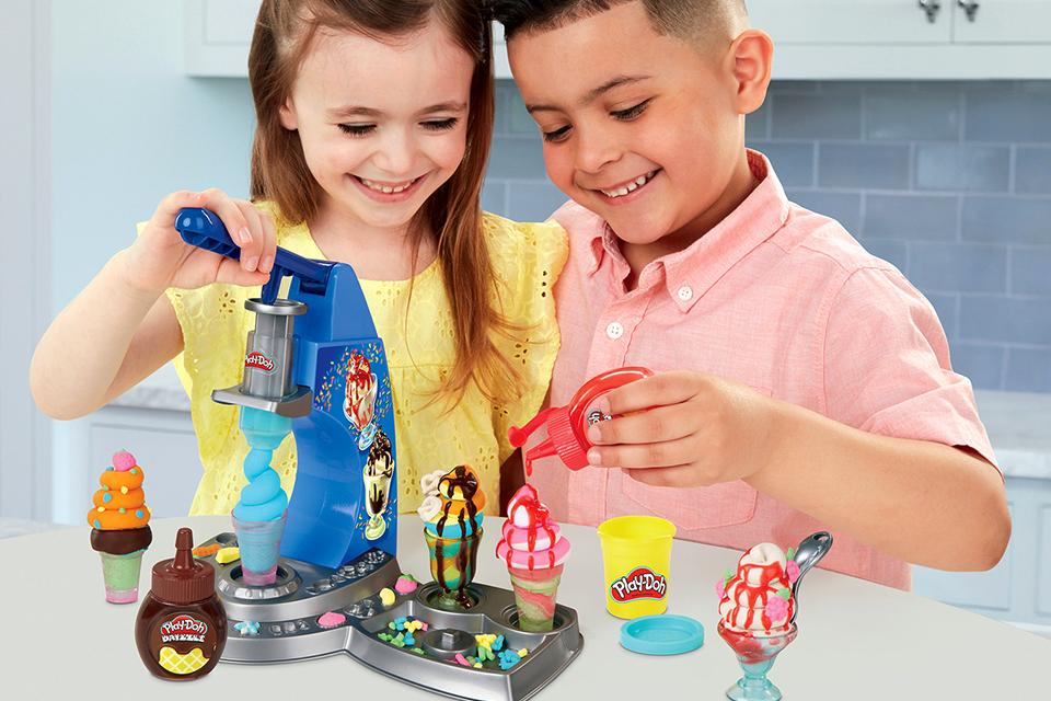 Little boy and girl making Play Doh ice creams with the Drizzy Ice Cream Machine Playset.
