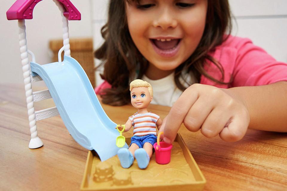 Girl playing with Barbie Skippers Babysitter doll slide playset.