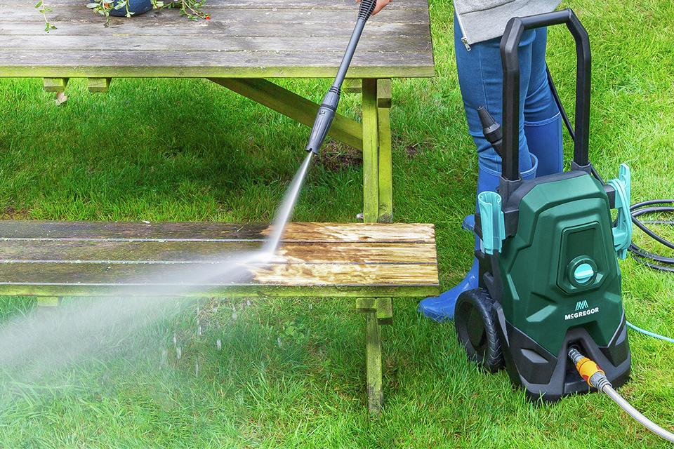 Gardener using a McGregor pressure washer to jet away dirt from a bench.
