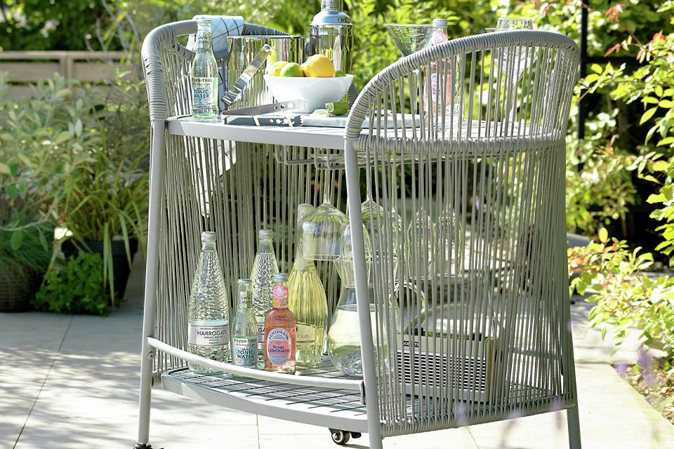 Grey drinks trolley in garden.