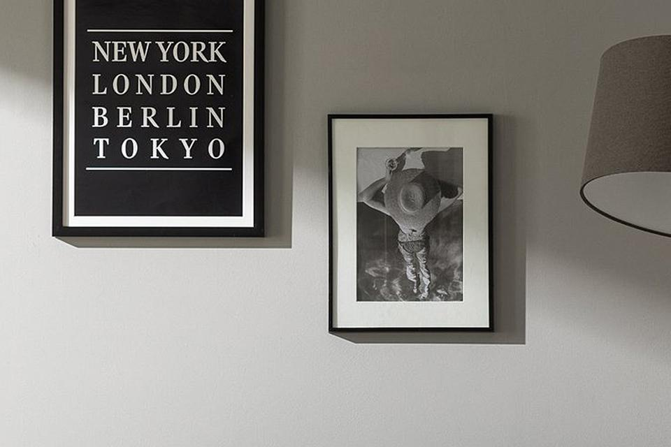 One frame hanging above another on a grey wall.