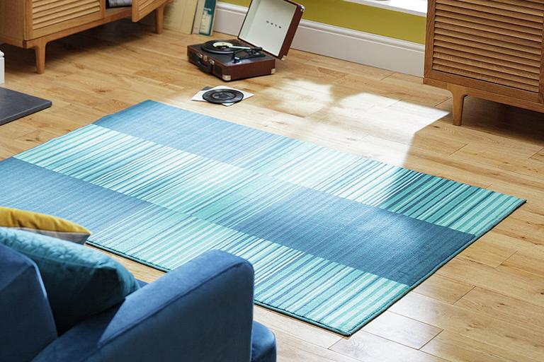Image of striped blue rug on wooden floor next to blue armchair.