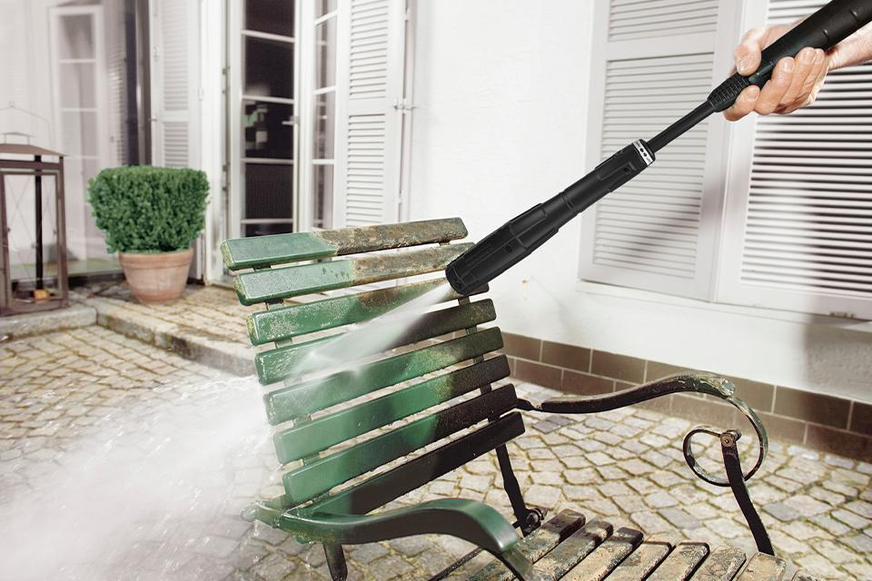 Pressure washer cleaning dirt off garden chair.