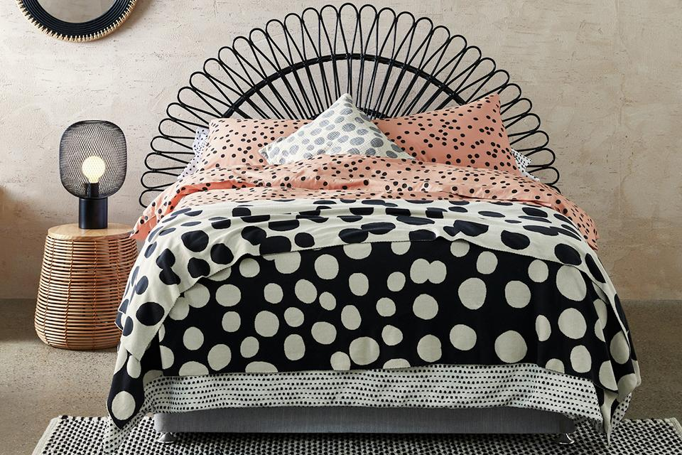 Black rattan headboard on bed with polka dot bedding