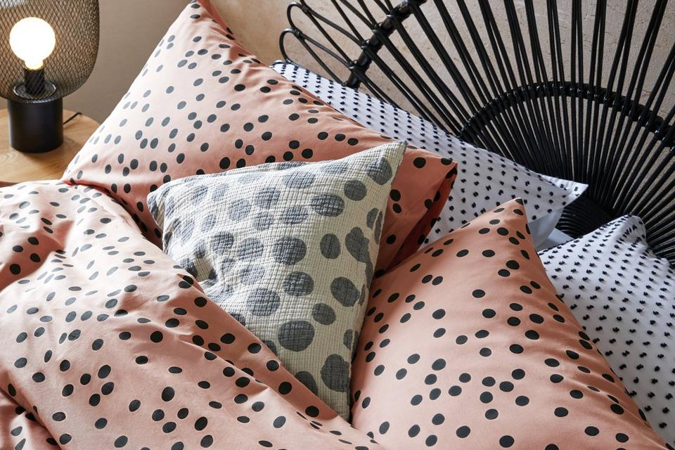 Pink polka dot bedding on black rattan bed.