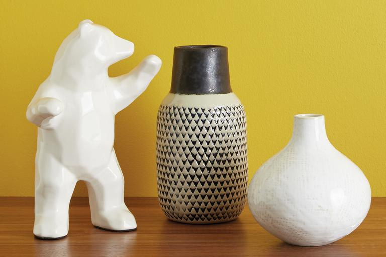 Two vases and an animal figurine against a mustard yellow background.