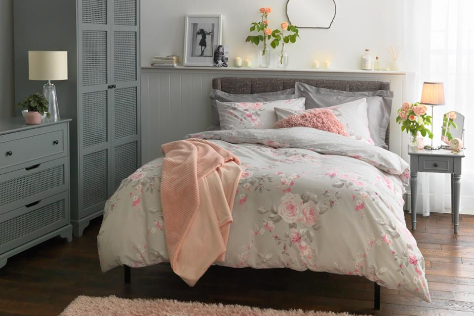 A bedroom featuring a bed dressed in floral bedding and grey bedroom furniture.