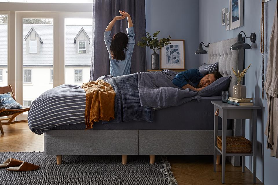 A grey bedroom setting with a woman waking up and stretching and a man still asleep next to her.