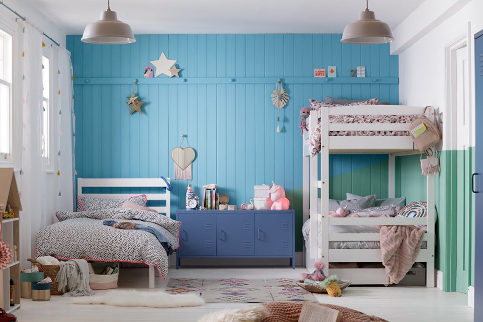 A child's bedroom with a bunk bed one side and single bed the other with blue walls.