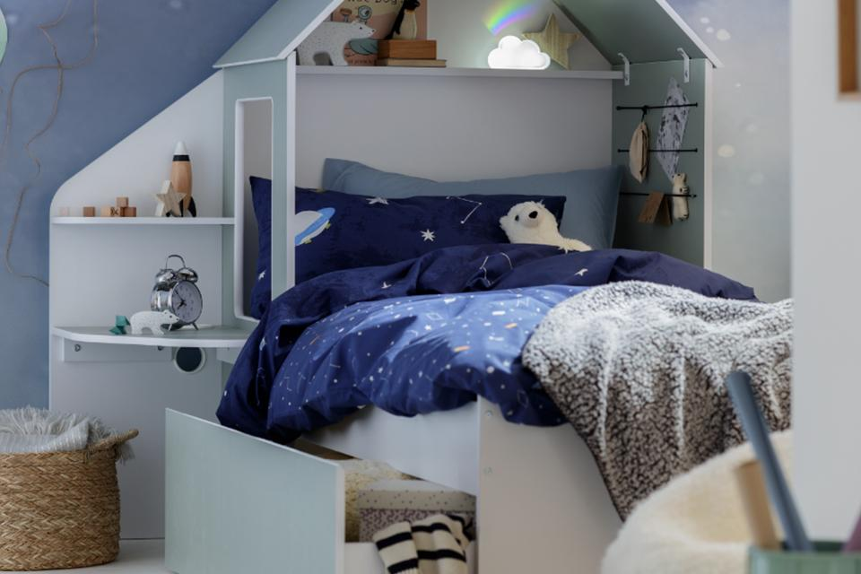 A child's bed with storage drawers and shelves attached and the headboard in the shape of a house.