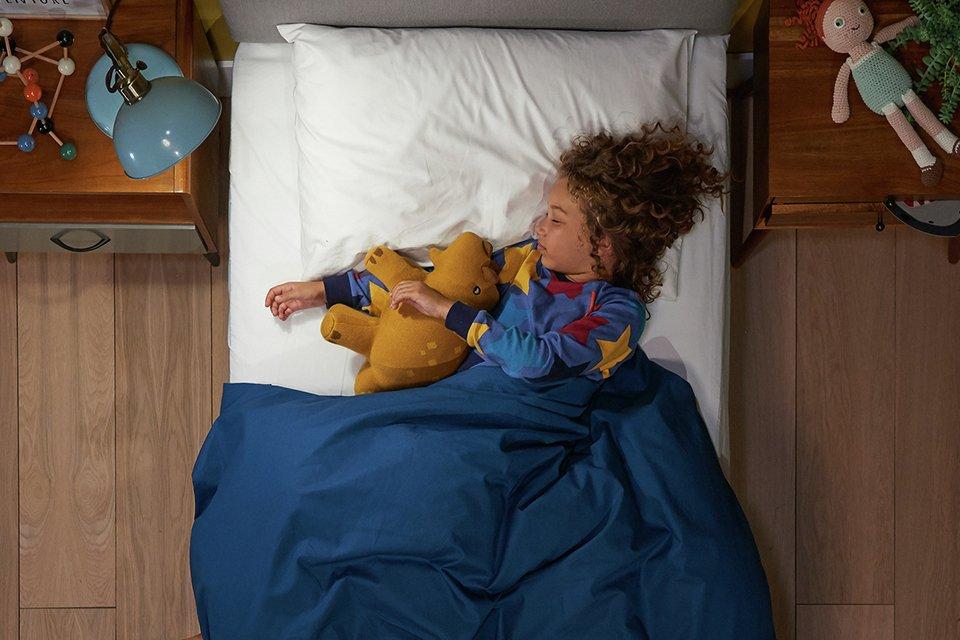 A child asleep on the Silentnight Healthy Growth kids classic mattress.