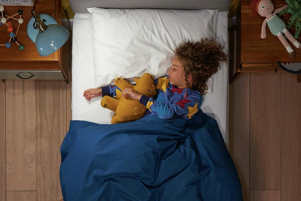 A child asleep on the Silentnight Healthy Growth kids classic mattress.