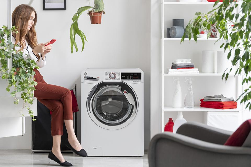 A lady on her mobile sitting by a washing machine waiting for it to finish.