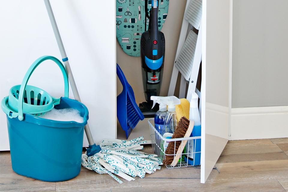 A cupboard open with lots of cleaning products including a mop and bucket and dustpan and brush..