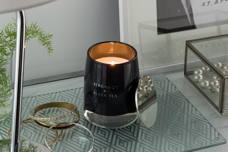 The Argos Home candle with lid in black on a table next to jewellery.
