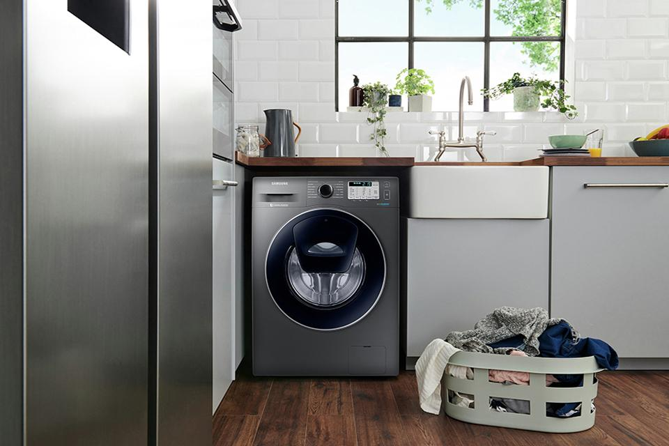 A graphite Samsung washing machine in a kitchen with a laundry basket in front.