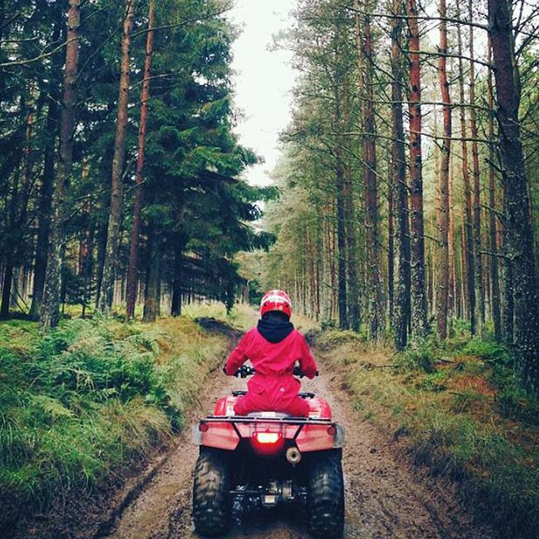 Back view of woman on go kart driving through forest.