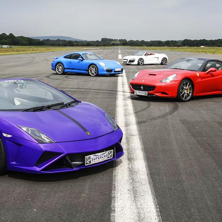 Purple, red, blue and white sport cars lined up on road.