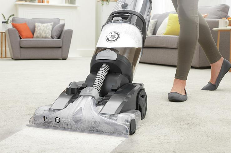 Woman using a carpet cleaner on a living room carpet.