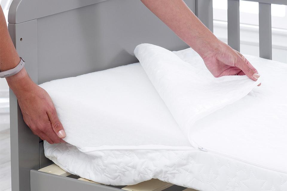 A cover being removed from a mattress.