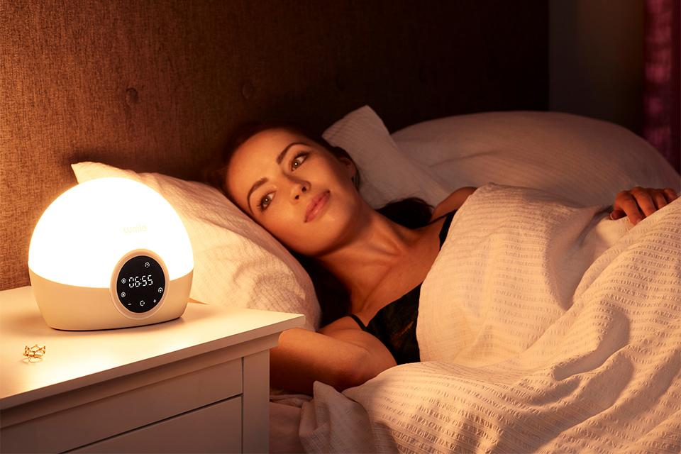 A woman wakes up next to her wake-up light.