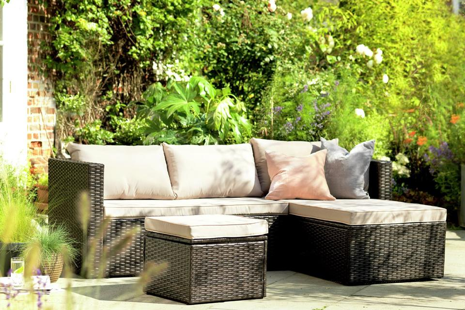 A rattan corner furniture set in the garden.