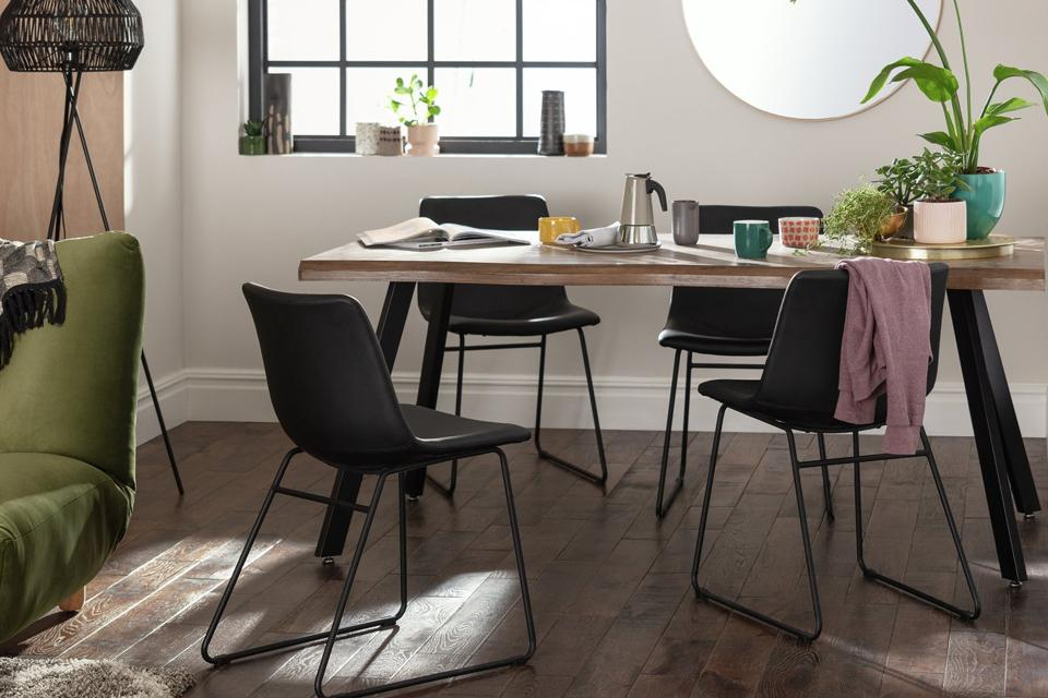 Four black dining chairs around a rectangular wooden dining table.