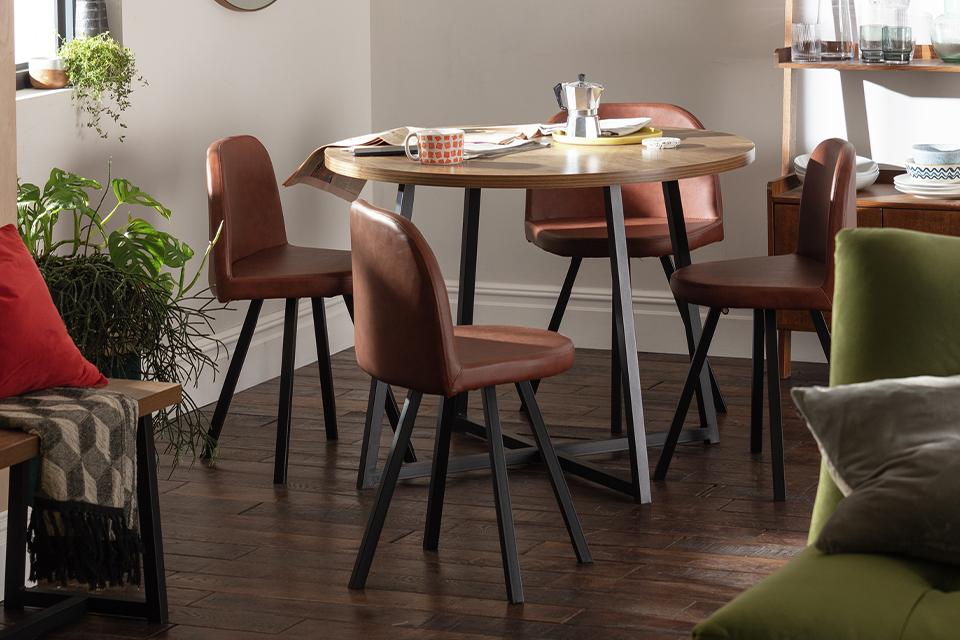 Round, wooden dining table with four leather chairs.
