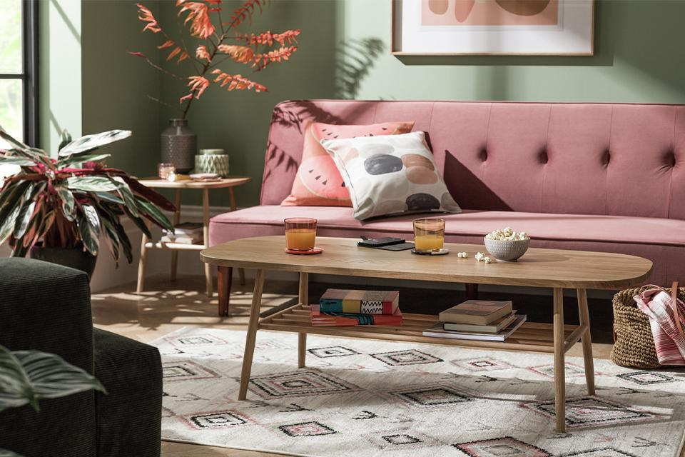 Wooden coffee table on a aztec patterned rug, in front of a pink sofa.
