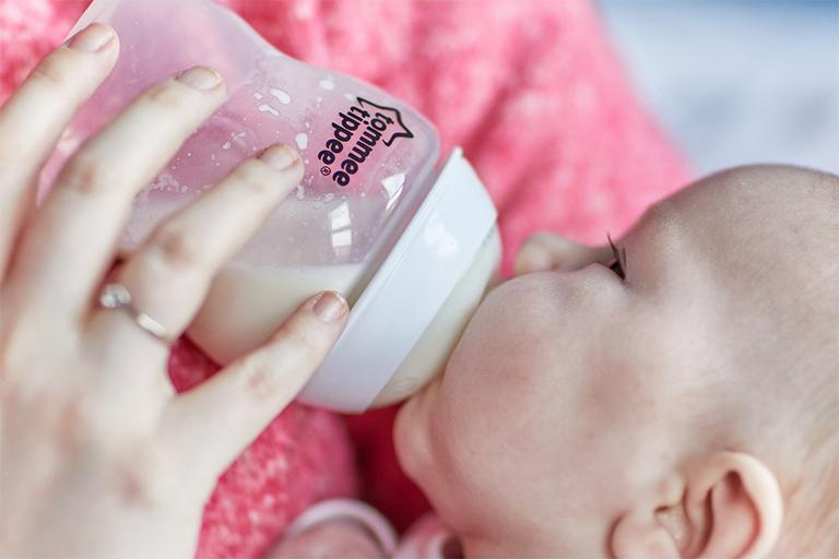 A baby drinks milk from a Tommee Tippee baby bottle. Both baby and bottle are held by someone wearing a pink jumper, with only shoulders visible.