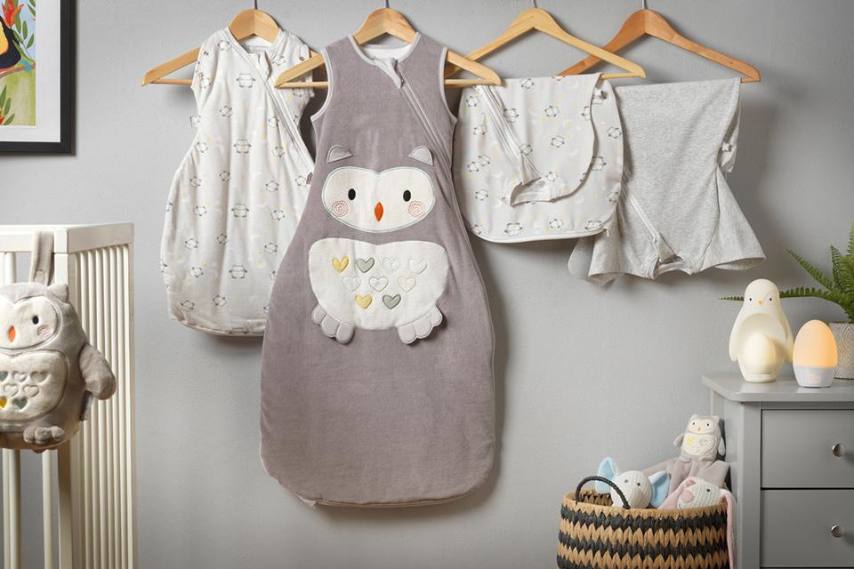 Image shows a selection of babies' sleepwear and blankets, displayed on hangers against a grey wall. On the left, a stuffed owl hangs on the bars of a white crib, while on the right, Tommee Tippee penguin and GroEgg night lights are placed atop a white chest of drawers.