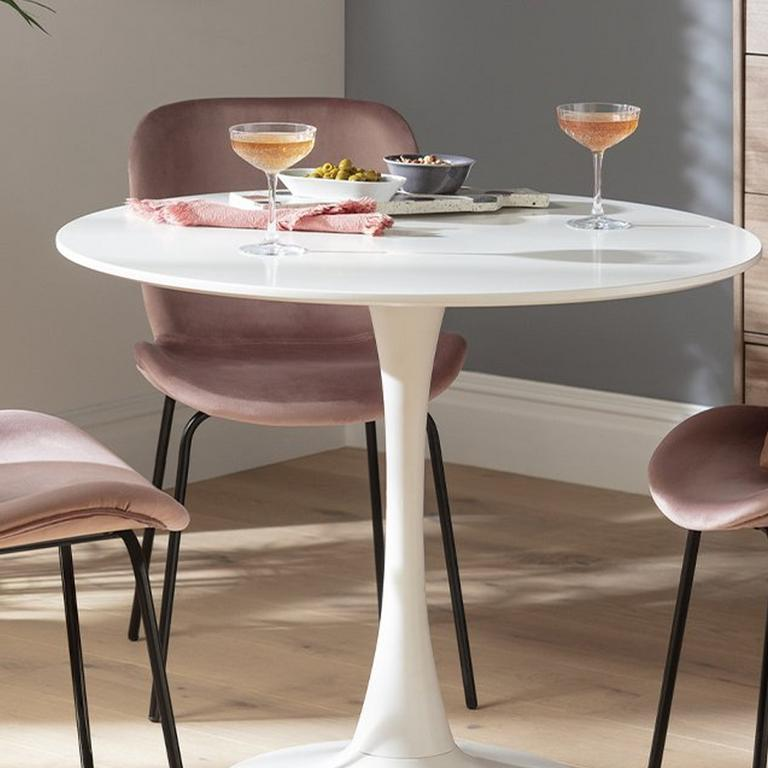 Image of three pale pink, velvent chairs around a round, white table with cocktail glasses on top