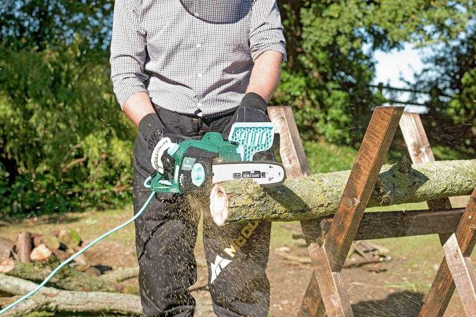 Man using McGregor electric chainsaw to cut up a log.