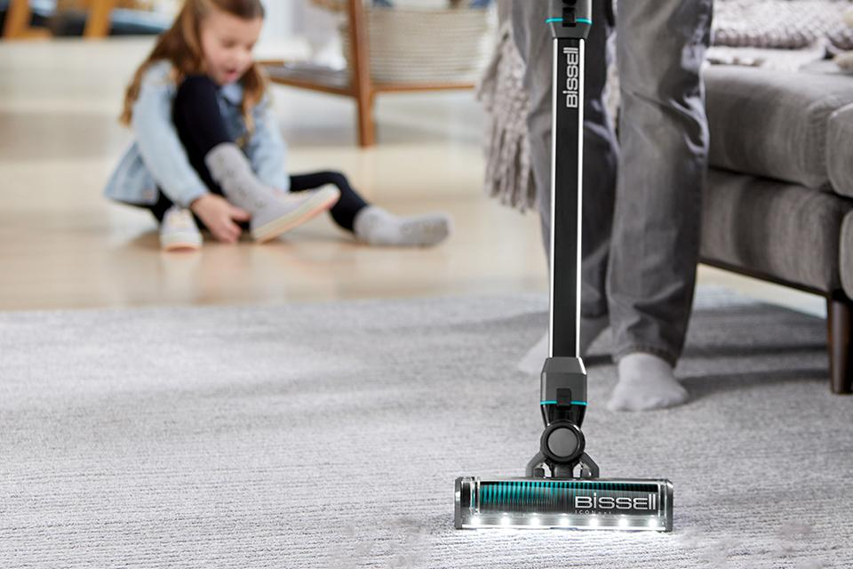 An adult is vacuuming a rug, whilst a child plays in the background.