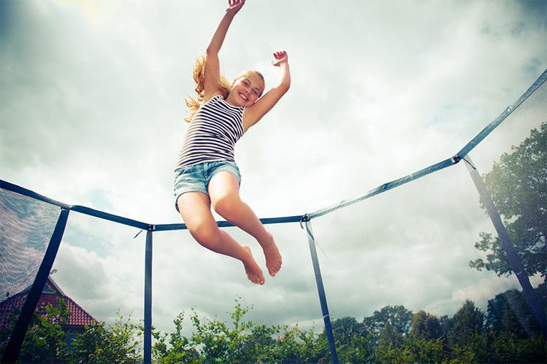 A girl jumping on a trampoline.