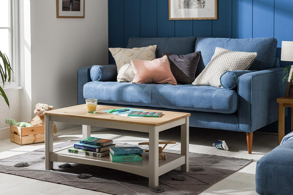 A cream and natural wood coffee table in front of a blue velvet sofa.