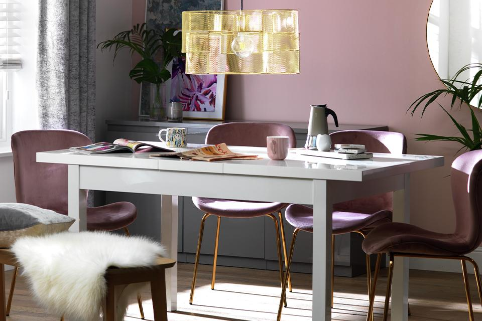 Pink velvet dining chairs around a white rectangular dining table.
