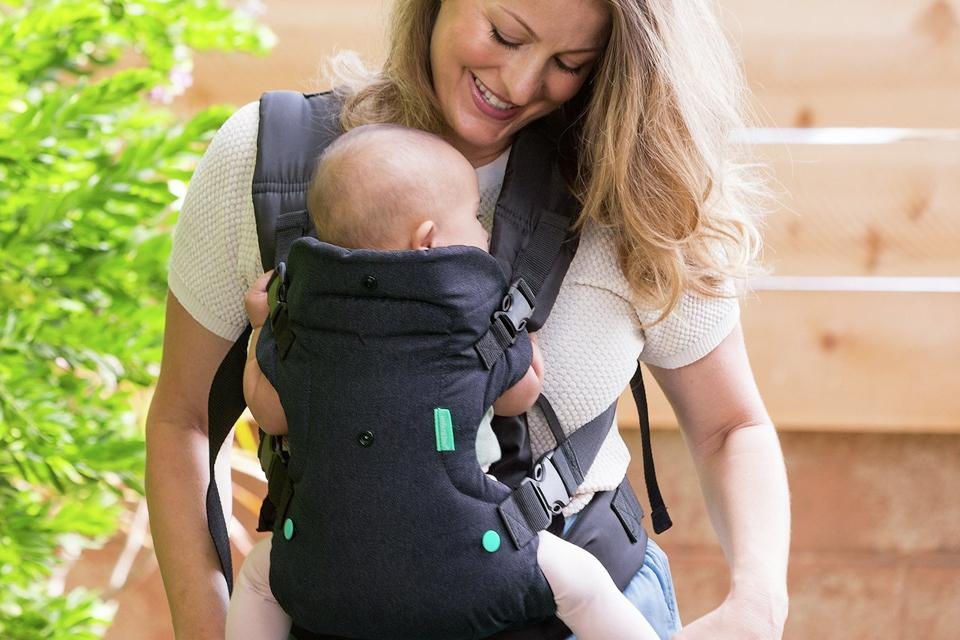 A newborn baby in a baby carrier.