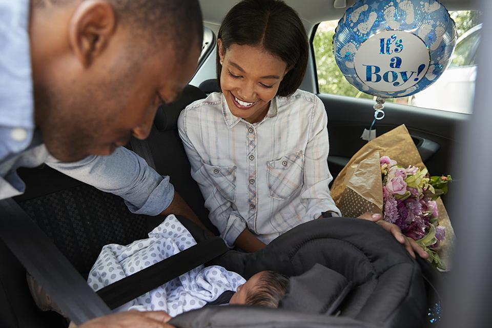 Parents securing their newborn baby in a car seat.