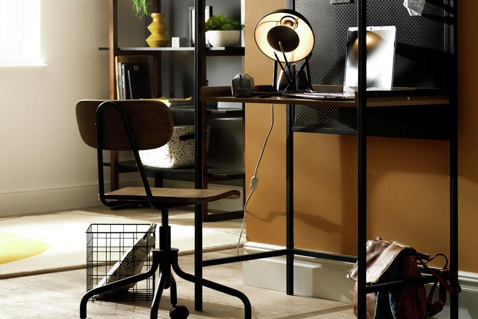 Office space with black desk, desk lamp and office chair.