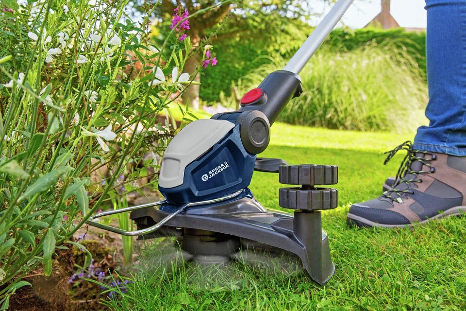 Man using grass trimmer to neaten lawn edge.