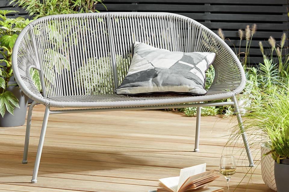 Grey roped garden bench on decking.