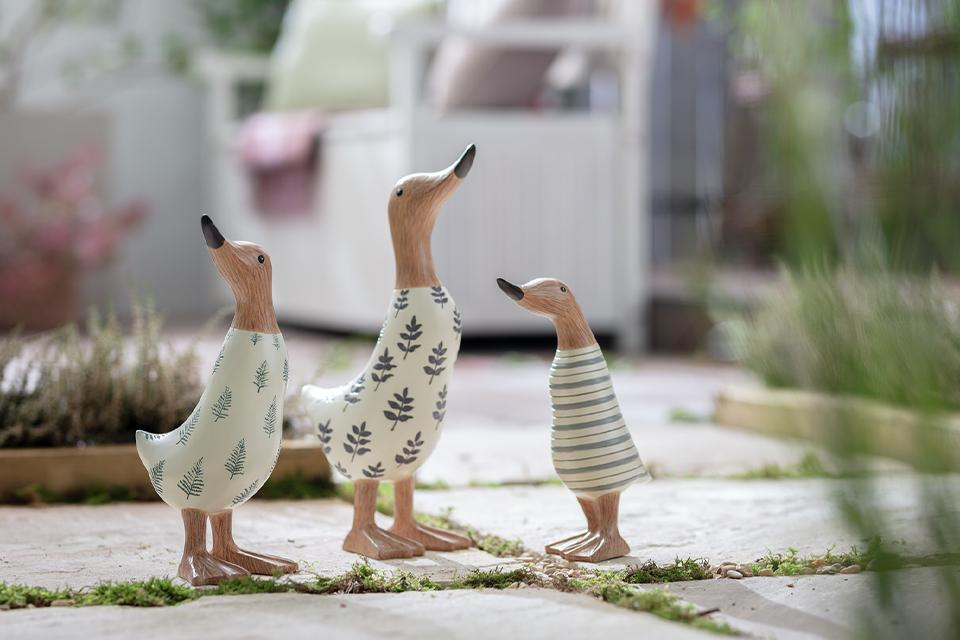 Three wooden ducks in garden.