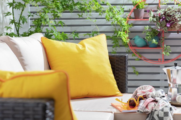 Rattan garden chair with cream and yellow cushions in garden.